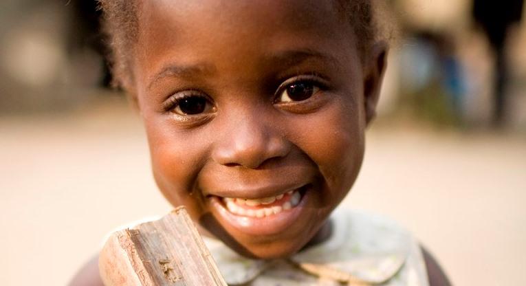 lapsi hymyilee kameralle.