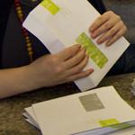 Pino kirjekuoria pöydällä, joita henkilö postittaa