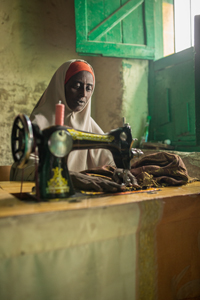 Sahra Mohammed Mohammud ompelee sukulaismiehensä liikehuoneiston nurkassa Erigavon kauppatorilla. Ompelijan ammattitaito takaa hänelle toimeentulon. Kuva: Ville Asikainen