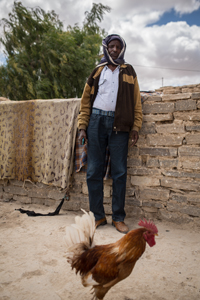 Entinen karjatilan omistaja Abdoullah Hassan Aateeye saa nyt, pakolaisena, tärkeää lisätuloa myymällä kananmunia. Kuva: Ville Asikainen