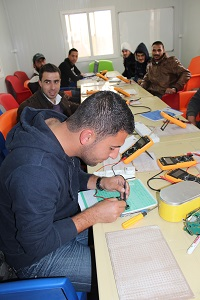 Basel Noserat opettelee matkapuhelimen korjaamista Za'atrin pakolaisleirillä Pohjois-Jordaniassa. Noserat kertoo testanneensa kurssilla oppimaansa ystäviensä vikaantuneisiin matkapuhelimiin. Kuva: Terhi Kinnunen