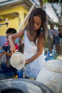 Seitsenvuotias Ellen Dinoy hakee juomavettä kirkkojen katastrofiavun vesipisteeltä Tindogin kylässä. Kuva: Ville Asikainen