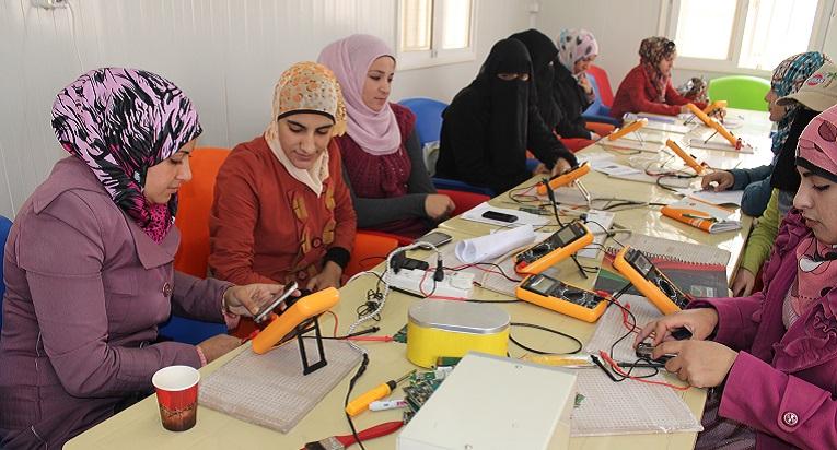 Syyrialaisia pakolaisnaisia kurssilla, jolla opiskellaan matkapuhelimen korjaamista. Kuva: Terhi Kinnunen