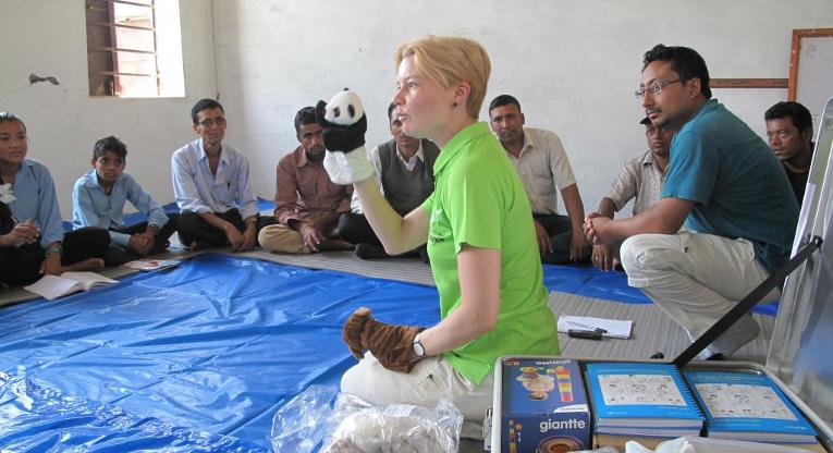 Medlem i beredskapsgruppen, specialläraren Johanna Kurki visar nepalesiska lärare hur man med hjälp av handdockor kan hjälpa barn att berätta om sina känslor och erfarenheter. Bild: Tuomas Väisänen.