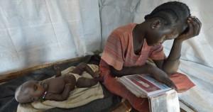 Nyanthem Mayol katsoo sukulaistensa valokuvia Sara-tyttärensä nukkuessa telttasuojassa Ajoung Thokin pakolaisleirillä huhtikuussa. Äiti ja tytär pakenivat väkivaltaisuuksia Bentiun kaupungista vuoden 2013 lopussa ja saapuivat leiriin viikkojen matkanteon jälkeen viime maaliskuussa.