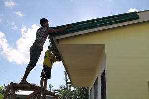Felomino Cabueños (vas.) ja Nilboy Ocale asentavat ränniä San Josen koulun uuteen luokkarakennukseen.