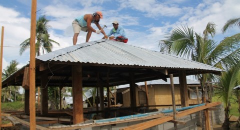 Servando Alliabas (left) and Joel Abeleno are constructing in Samar-island a four-cornered roof, which has proven resistant to strong winds.