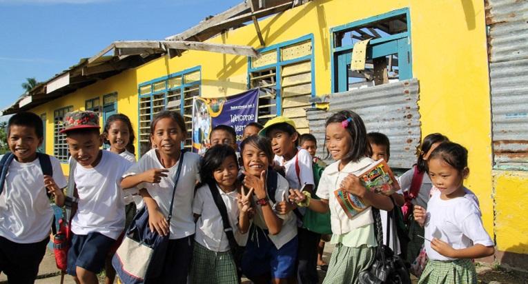 San Pedron koulun oppilaat poseeraavat viime marraskuisen taifuuni Haiyanin tuhoaman koulun osan edessä.