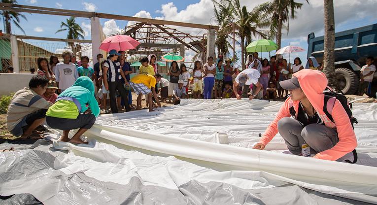 Utlandshjälpens humanitära arbete: bilden är tagen på Filippinerna i oktober 2013, en månad efter tyfonen. Jamilah Mustapha (främst t.h.) i byn Suri på ön Cebu, visar hur man reser ett familjetält. Organisationen PDRN som hör till ACT-alliansen, kunde med stöd från Kyrkans Utlandshjälp distribuera tält till de mest utsatta såsom ensamförsörjare och åldringar. ACT-alliansen har bistått över en miljon människor på de drabbade öarna Samari, Leyte, Cebu, Panay och Negros. Nätverket har försett 430 000 människor med livsmedel, 350 000 har fått filtar och biståndsförpackningar vilka innehåller hygienartiklar och kökstillbehör. Bild: Ville Asikainen