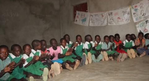 Songokin alakoulun oppilaat istuvat savilattialla ja kertaavat kuorossa, kun opettaja osoittaa itse tehdyiltä opetustauluilta kotieläinten nimiä.
