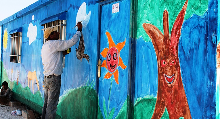 A volunteer painting learning facility (caravan) in Azraq camp. Photo: Muhammad Smadi