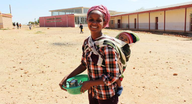 Miliete Tsefa, joka työskentelee opettajaopiskelijoiden tukena Mai Nefhissa, on matkalla lounastauolle lapsensa kanssa. Taustalla näkyy kampusalueen uusi kirjasto.