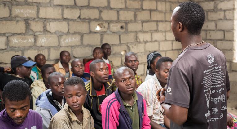Entinen lapsisotilas Heritier Nguma kertomassa omasta tarinastaan ja ETN:n koulutuksen tärkeydestä uudelle juuri aloittavalla oppilasryhmälle Masisin ETN-keskuksen keskeneräisessä luokkahuoneessa. Kuva: Ville Asikainen.