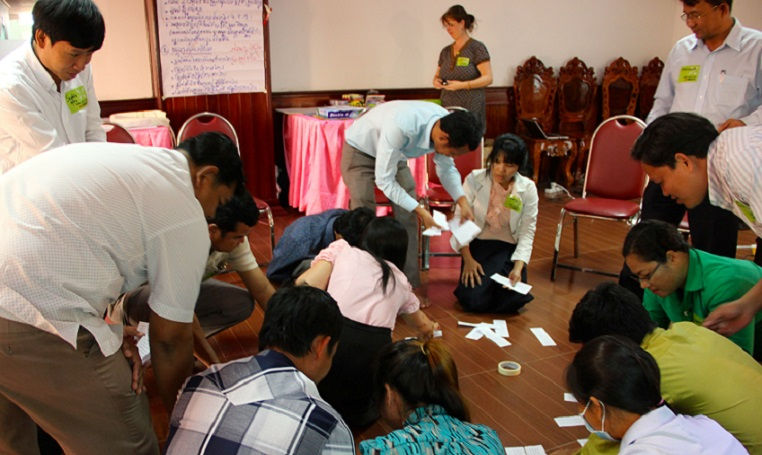 In the training, teachers and officials from the Ministry of Education and districts are studying together, which is uncommon in Cambodia. In the background, Vichet Un and Theary Chhoeun are concentrating on a group assignment.