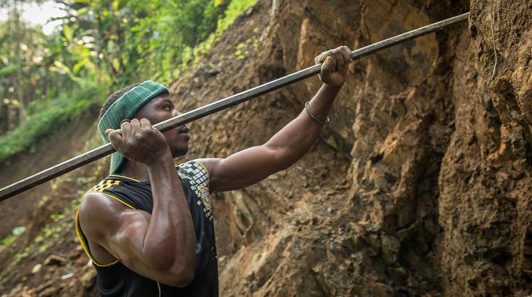 Nkuba bryter själv den sten som skall läggas på vägen. Han gör det med hacka och järnspett.