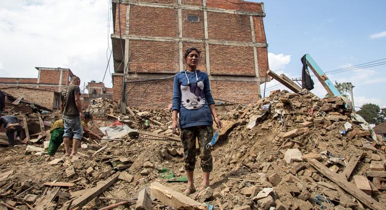 Nikisha Bhalandyu seisoo entisen kotitalonsa raunioilla Kathmandunlaakson Bhaktaburissa huhtikuussa 2015. Kuva: Antti Helin.