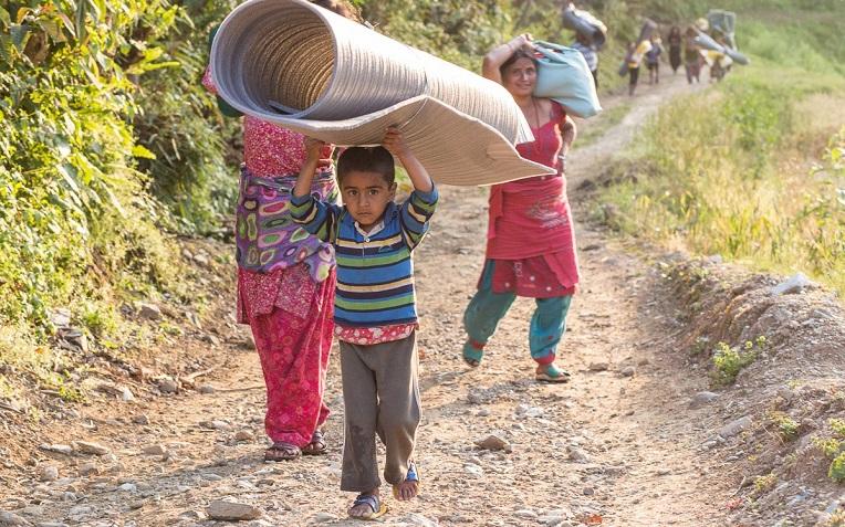 Avustustarvikkeet selässä, edessä pitkä kävely kotitalolle.