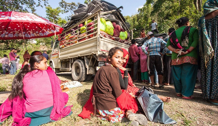 Kyläläiset ovat kerääntyneet katselemaan avustuspakettien jakamista. Tunnelma on melkein kuin piknikillä.