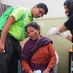 Sanju Bajracharya puhdistaa haavaa rouvan korvassa Ulkomaanavun kumppanin UCEP:n terveysvastaanotolla. Vasemmalla Ulkomaanavun maakoordinattori Lila Bashyal. Kuva: Johanna Tervo.