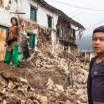 Sabita Moktan (vas.) raunioituneen talonsa edessä Bhattedandan alueella Nepalissa. Kuva: Antti Helin.