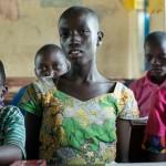 """""""Koska tänään on African Child Day, on meillä vain vähän oppilaita luokassa. Välillä keskittyminen on vaikeata, koska luokkakoot ovat niin suuria"""", kertoo 13-vuotias Elia (kesk.) kesäkuun puolivälissä. Hän opiskelee Ntezirayon koulussa Rwamwanjassa. Ulkomaanapu on rakentanut koulun kaksi luokkahuonetta. Kuva: Juha Haapala."""