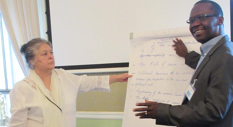 Kansalaisjärjestöjen edustajat Mahdooba Seraj (Afganistan) ja John Caulker (Sierra Leone) esittelevät konferenssin osallistujille ryhmäkeskustelussa nousseita ratkaisuehdotuksia kansalaisyhteiskunnan osallisuuden vahvistamiseksi. Kuva: Minna Vähäsalo.
