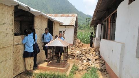 Väliaikainen koulu ja vaurioitunut koulurakennus, joka ei ole enää turvallinen.
