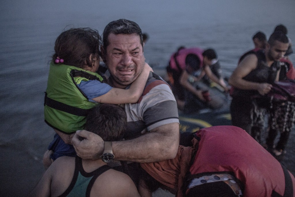A Syrian refugee from Deir Ezzor, holding his son and daughter, breaks out in tears of joy after arriving via a flimsy inflatable boat crammed with about 15 men, women and children on the shore of the island of Kos in Greece, Aug. 15, 2015. Photo: Daniel Etter/The New York Times