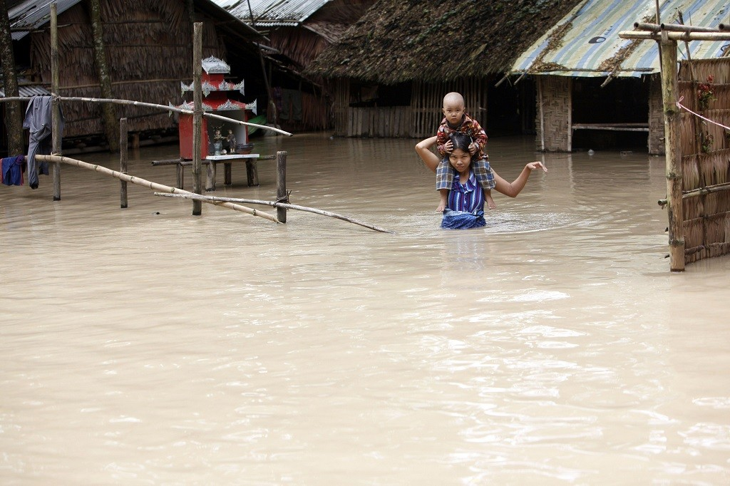 A woman carries her child from their half-submerged house in Nyaung Tone, Ayeyarwaddy Delta, about 60 miles southwest of Yangon, Myanmar. Friendly nations and international relief organizations are mobilizing to give disaster assistance to Myanmar, where 69 people have died and another 260,000 been affected by widespread flooding fed by more than a month of heavy monsoon rains and a cyclone. (Photo: AP/Khin Maung Win)