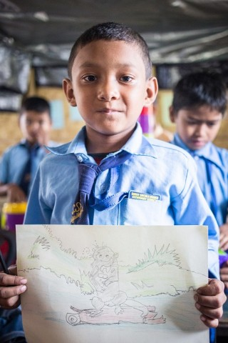 Suresh Tamang, 10 years old, is an aspiring young artist. He is showing his drawing of a beaver.