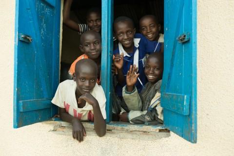 Lapset vilkuttavat koululuokasta. Kirkonulkomaanapu on rakennuttanut Ntezirayon peruskoululle kaksi koululuokkaa, mutta apua tarvitaan edelleen sillä samassa luokassa saattaa opiskella jopa 200 oppilasta.