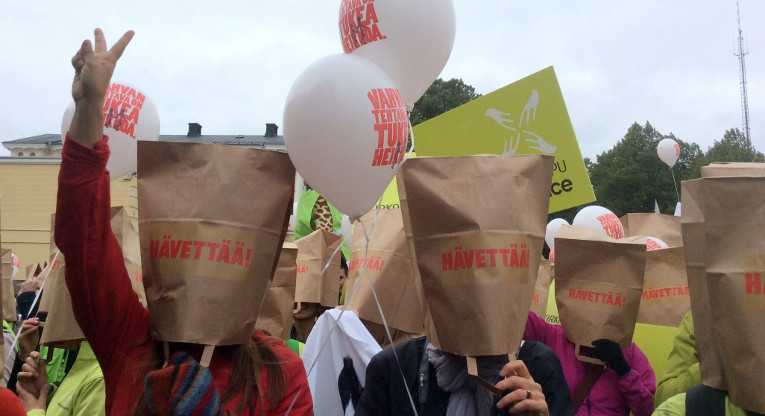 Yli tuhat ihmistä osallistui Me välitämme -mielenilmauksene kehitysyhteistyön puolesta. Lopuksi mielenosoittajat vetivät paperipussit päähänsä - Suomen luistaminen kansainvälisistä sitoumuksista hävettää. Kuva: Veera Pitkänen.