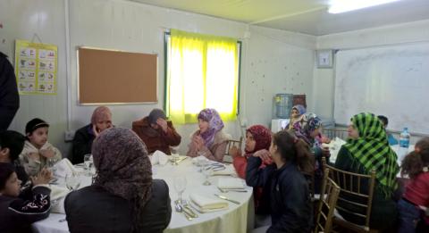 Osa Jordanian pakolaileirien asukkaista ovat jakamassa matkaansa saatuaan kiintiöpakolaisen paikan esimerkiksi kanadasta. Kirkon Ulkomaanavun hankkeissa vpaahetoistyötä tehneet pakolaiset juhlistivat yhteistyötä Azraqin leirillä juhla-aterian ja kuniakirjojen jaon merkeissä. Kuva: Olli Pitkänen.