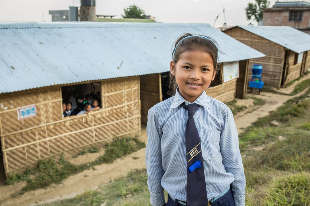 9-year-old Srijana Tamangin at the Bal Bikas primary school. The temporary learning spaces behind her were constructed by Finn Church Aid.