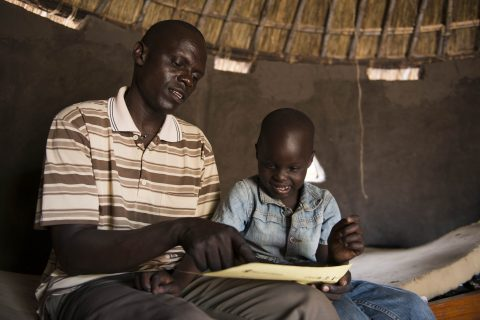 Thesame and his father John inside their tuku at a refugee settelemnt in Adjumani.