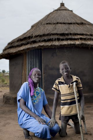 Chawich and his mother outside their tuku hut. Chawich's wish of an education will finally be realised in the Inclusive Education facility funded bv FCA.