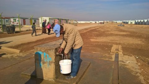 Abu Omar retrieving water from a well.