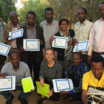 Course participants hold their diplomas with pride.