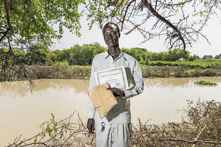 Maanviljelyskoulutukseen osallistunut Baba Korok Logidang näyttää todistustaan. Kuva: Ville Palonen