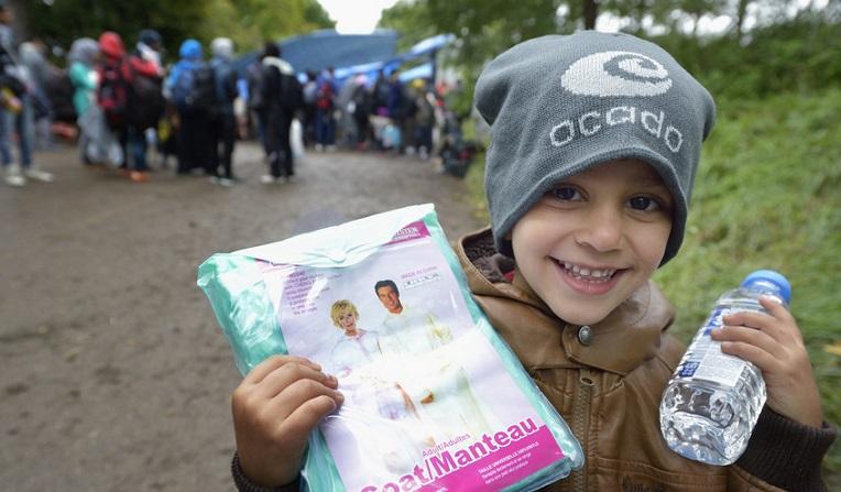 Pakolaisten joukossa Serbiaan saapunut poika pitelee avustuksena saamaansa sadetakkia. (Paul Jeffrey)