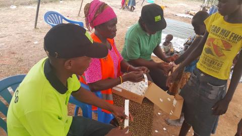 Ulkomaanavun työntekijät auttoivat kiinnittämään rannekkeita Pohjois-Ugandan vastaanottokeskuksessa. Rannekkeiden avulla varmistetaan, että jokainen pakolainen rokotetaan.
