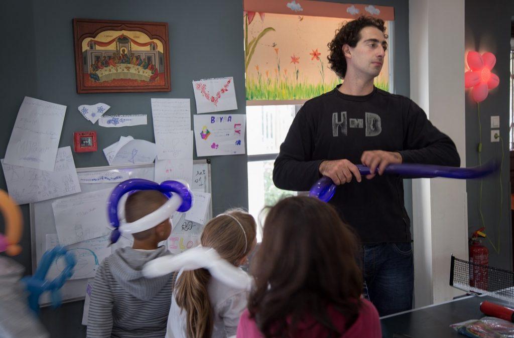 Dimitrionin koulutuskeskuksen ohjaaja tekee lapsille päähineitä ilmapalloista. Seinällä näkyy kreikkalaisten lasten ja pakolaislasten viestittelyä. Lapset ystävystyivät kesällä, mutta koulun takia ryhmät käyvät nyt eri aikoihin koulutuskeskuksessa, ja kuulumisia vaihdellaan lapuilla. Kuva: Ville Nykänen