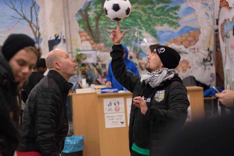 Jan Saddei koordinoi pakolaisten jalkapalloharjoituksia Münchenissä Buntkicktgut-järjestössä. Kaj Kunnas ihailee Janin pallotekniikkaa Peace United -turnauksen yhteydessä.