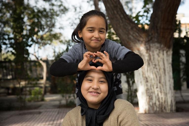 Eleonasin pakolaisleirillä Ateenassa asuvat 8-vuotias Fatima (ylhäällä) ja 11-vuotias Maryam oppivat tuntemaan toisensa Kirkon Ulkomaanavun koulutusaktiviteettien kautta.