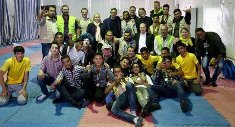 Sirkuskoulun vanhemmat oppilaat ja ohjaajat ryhmäkuvassa suomalaisten vieraiden kanssa.