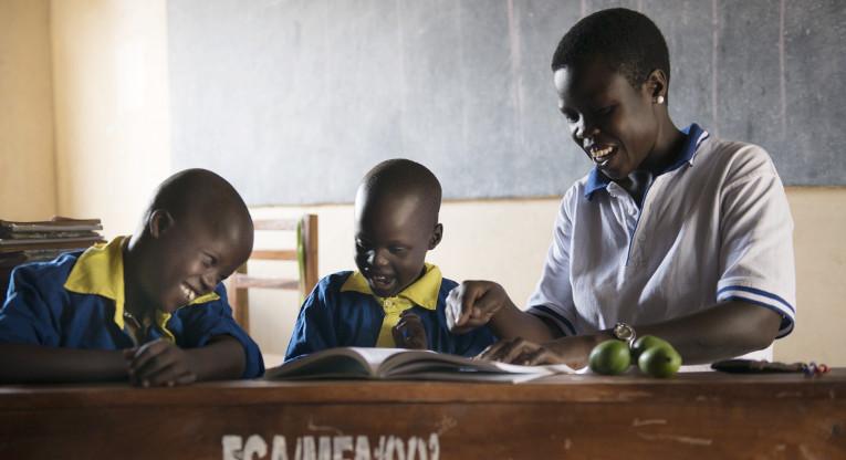 Opettaja ja oppilaat koululuokassa Ugandassa.