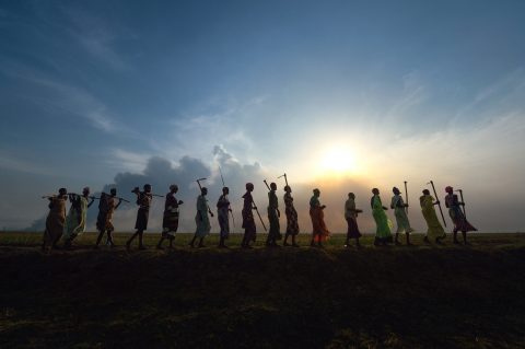 A group of women sing and dance as they walk home atop a dyke they constructed to control flooding in South Sudan's Jonglei State. Photo: Paul Jeffrey / ACT