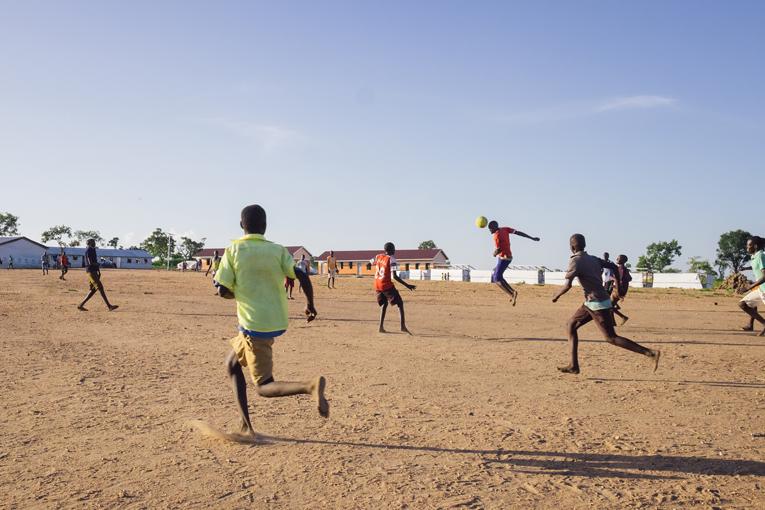 Mycket av livet bland de sydsudanesiska flyktingarna kretsar kring barnen. Av en miljon flyktingar är över 60 procent under 18-åringar. Bilden är tagen på fotbollsplanen vid Kyrkans Utlandshjälps skola som ligger på andra sidan vägen från Muja Roses lerhydda.
