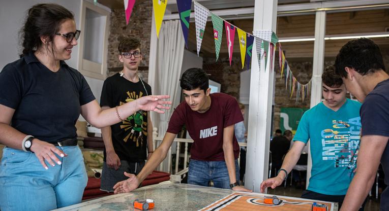 reikassa paikallisille ja pakolaisnuorille järjestetyssä työpajassa opiskelijat koodasivat robottiautoja suorittamaan erilaisia tehtäviä.