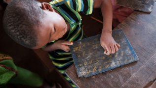 Keskiafrikkalainen koululainen harjoittelee kirjaimia.